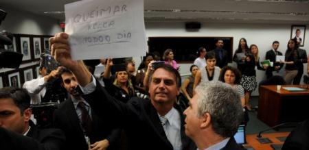 13mar2013---durante-sessao-da-comissao-de-direitos-humanos-da-camara-o-deputado-jair-bolsonaro-pp-rj-mostra-cartaz-a-manifestantes-onde-esta-escrito-queimar-rosca-todo-o-dia-a-primeira-sessao-da-1363205848541_615x300